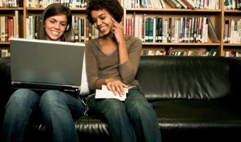 Two students sitting on a couch in a library with a laptop