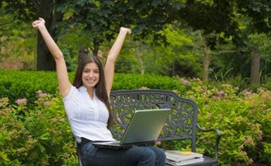 pretty young woman, finished her work, excited about good news, outdoors in summer studying with books and laptop computer on bench in park